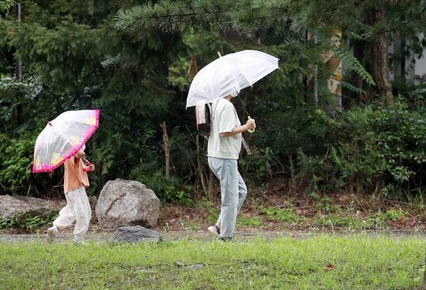 8월 31일 오후 경기도 과천시 서울대공원 인근에서 한 아이와 엄마가 우산을 쓰고 걸어가고 있다.  ⓒ뉴시스·여성신문