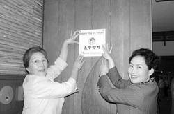 2006년 5월 여성재단 캠페인의 일환으로 요식업체 (주)놀부에서 '딸들에게 희망을 주는 가게 28호'로 약정을 한 후 놀부음식점 앞에서 김순진 사장(오른쪽)과 함께 현판을 달고 있는 모습.
