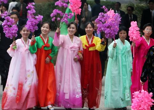 곱게 한복을 차려 입은 평양 여성들이 지난 10월 '2007년 남북정상회담'을 위해 방북한 남측 관계자들을 태운 버스를 향해 꽃술을 흔들며 환영하고 있다. ⓒ청와대사진기자단