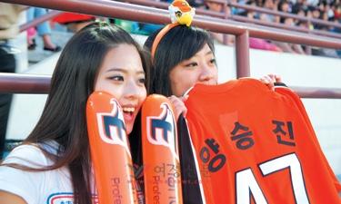 '한화 이글스'와 '넥센 히어로즈' 경기가 열린 8일, 서울 양천구 목동야구장에서 여성 팬들이 자신이 좋아하는 선수의 유니폼을 들고 응원을 하고 있다.