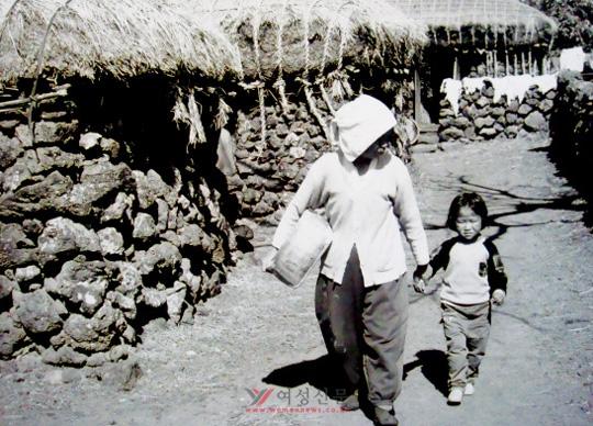 손녀와 외출 - 마실(외출) 가는 할머니가 보름구덕을 옆구리에 끼고 손녀의 손을 잡고 초가 올레를 걸어 나오고 있다.