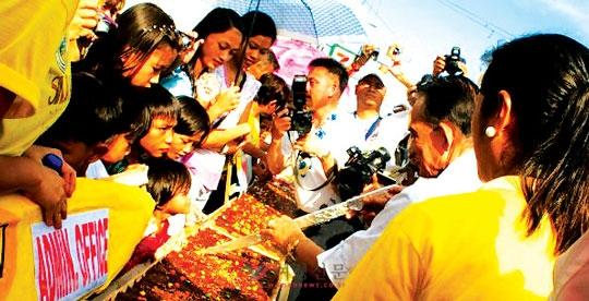 필리핀 로사리오 바탕가스시 시장이 피에스타에 참가해 찹쌀로 만든 대형 떡 '시눅마니'를 자르고 있다.