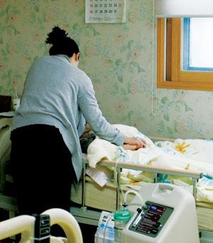 86세 아버지의 임종을 온 몸으로 끌어안고 지키는 딸. 1년 반 전 은성너싱홈에 들어온 아버지를 돌보면서 딸은 해묵은 애증을 풀고 마음 편히 아버지를 보냈다고 한다. ⓒ정대웅 여성신문 사진기자(asrai@womennews.co.kr)