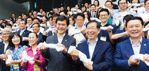 박원순 서울시장과 주민참여예산위원들이 지난 7월 서울인재개발원에서 열린 위촉식에서 마른 수건도 짜낸다는 의미의 퍼포먼스를 하고 있다. ⓒ서울시 제공
