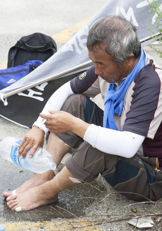 단원고 2학년 이승현군의 아버지 이호진씨가 쉬는 시간 발에 물을 부으며 열기를 식히고 있다. 이씨의 발은 물집으로 부르터 있었다.