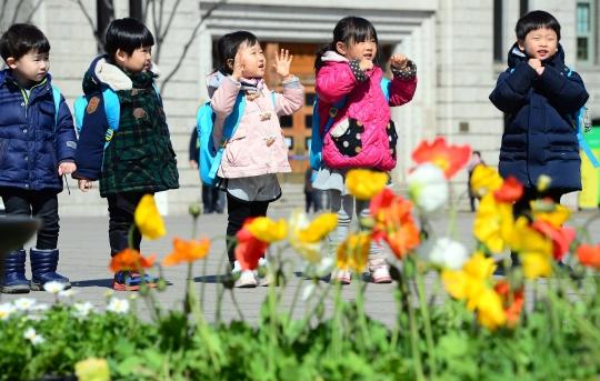 월요일인 16일도 포근한 봄 날씨가 이어지겠다. /본격적인 봄 날씨를 보인 지난 13일 오후 서울광장에서 화분에 식재될 꽃을 뒤로 아이들이 놀고 있다. ⓒ뉴시스·여성신문