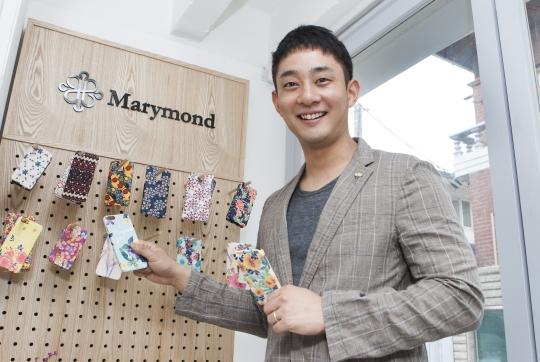 마리몬드 휴대폰 케이스 제품을 들고 선 윤홍조 마리몬드 대표. ⓒ이정실 여성신문 사진기자