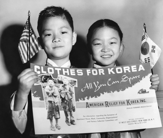 아메리칸 릴리프 퍼 코리아(ARK)가 1953년 옷 수집 캠페인을 위해 만든 포스터를 들고 있는 그레이스 김(오른쪽)-존 김 남매. ARK는 전쟁 구호민을 위한 이 캠페인을 위해 포스터 2만5000개를 제작했다. '뉴욕 타임스' 53년 3월17일치에 실린 사진. ⓒ뉴욕타임스