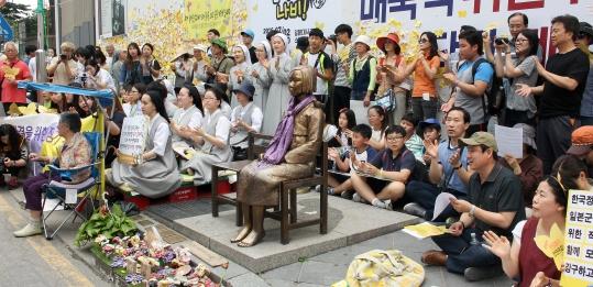 22일 오후 서울 종로구 중학동에서 열린 '제1236차 일본군성노예제 문제해결을 위한 정기 수요시위'에 참석한 시민들이 노래에 맞춰 박수를 치고 있다. ⓒ변지은 기자