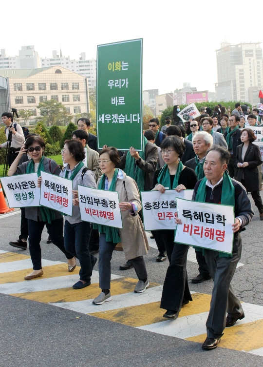 최경희 이화여대 총장이 사퇴한 19일 서울 서대문구 이화여자대학교에서 교수들이 기자회견을 마친 뒤 손팻말을 들고 행진하고 있다. ⓒ변지은 기자