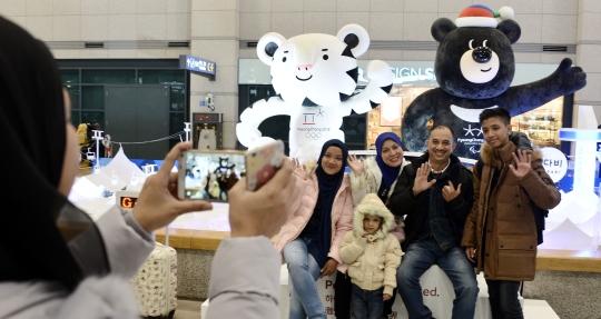 2018 평창동계올림픽(2018년 2월 9~25일)을 1년여 앞둔 8일 인천공항 도착장에 마련된 홍보부스에서 외국인 관광객들이 마스코트인 수호랑과 반다비 대형인형을 배경 삼아 기념촬영을 하고 있다. ⓒ뉴시스·여성신문