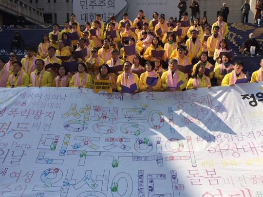 정의당은 3.8세계여성의날을 기념해 4일 서울 종로구 세종문화회관 앞에서 개최한 '100인의 합창 및 여성정책 발표' 행사에서  '성평등이 민주주의의 완성이다'라는 글귀의 대형 현수막에 핸드 페인팅 퍼포먼스를 진행했다. ⓒ여성신문