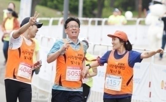 5km 부문에 참가한 시각장애인마라톤클럽 회원이 동반주자와 함께 골인점을 향해 달리고 있다.