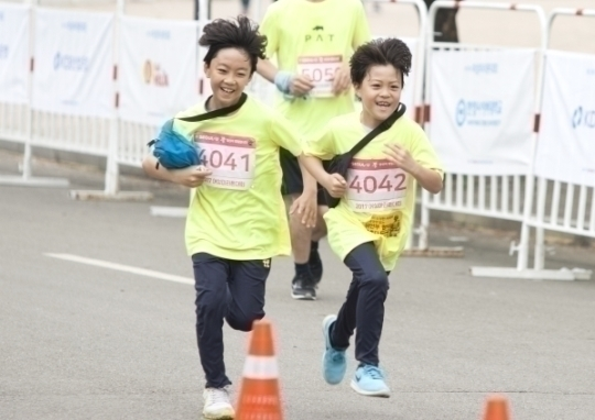 5km 부문에 참가한 어린이들이 골인점 앞에서 전력질주하고 있다.