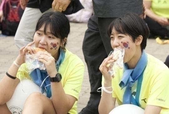 경기를 마친 참가자들이 간식을 먹으며 축하공연을 보고 있다.