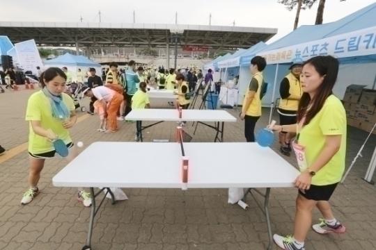 참가자들이 찾아가는 체육관부스에서 탁구를 하고 있다.