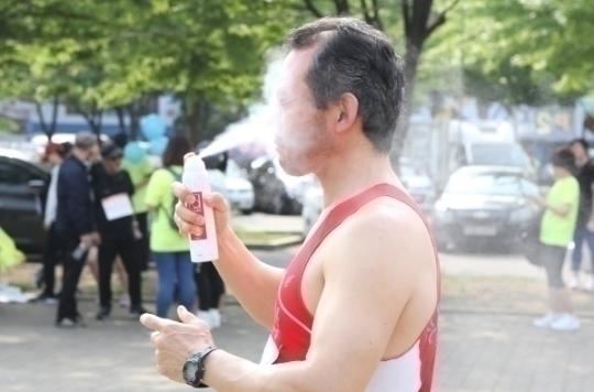 대회 출발 전 참가자가 얼굴에 선스프레이를 뿌리고 있다.