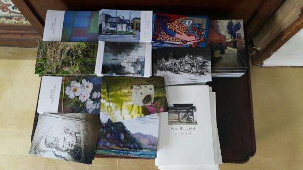 """문화공간100 """"어느날...골목"""" 100일간 릴레이로 전시될 작가들의 개인전을 소개하는 엽서가 관람객을 위해 준비되어 있다."""