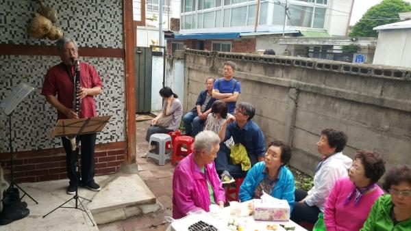 """지난 12일 춘천시 근화동에서 문화공간100 """"어느날...골목"""" 오프닝 행사를 기념해 연주가 김진묵의 공연이 펼쳐지고 있다."""