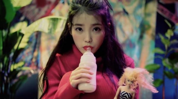 """아이유 '스물셋' 뮤직비디오의 한 장면. 아이유가 젖병을 빨다 여자 인형에 우유를 뿌리는 장면이 나와 """"과한 롤리타 설정""""이라는 비판을 받았다."""