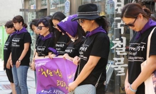 22일 군산시 대명동 화재참사 건물 앞에서 순례단이 희생자들을 위한 묵념을 하고 있다.
