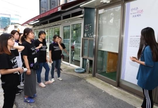 민들레순례단이 21일 선미촌 리본 프로젝트 기획전시가 열리고 있는 선미촌 696번가 성매매업소 앞에서 관계자에게 설명을 듣고 있다.