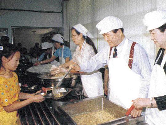 '원래 부드러운 사람'인데 모략을 받아 왜곡된 모습으로 비쳐졌다는 김대중 총재. 초등학교 어린이들의 급식을 돕고 있다.