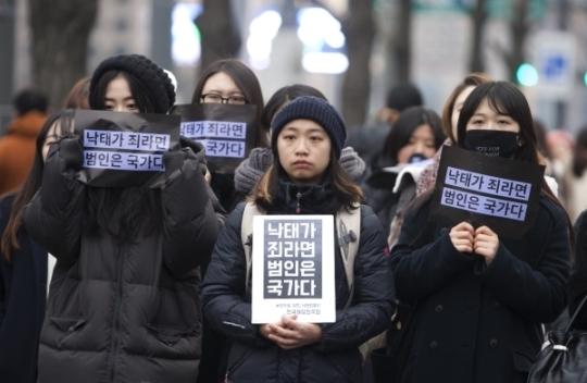 검은 시위 참가자들이 피켓을 들고 자유발언을 듣고 있다.