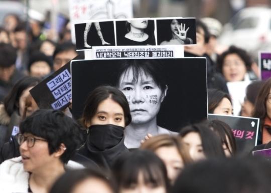 검은 시위 참가자들이 직접 만든 피켓을 들고 행진하고 있다.