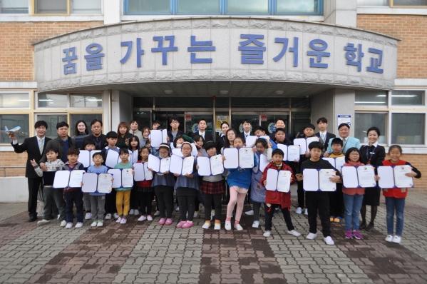 '하늘사랑 영어교실'에 참가한 대한항공 직원들과 용유초등학교 어린이들이 기념사진을 찍고 있는 모습 ⓒ대한항공