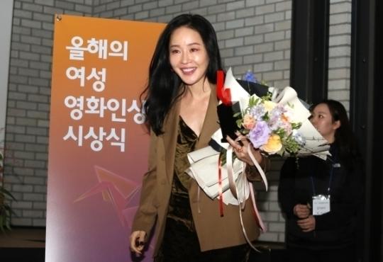 올해의 여성영화인상에서 엄지원이 연기상 수상 후 축하꽃다발을 안고 무대를 내려오고 있다.
