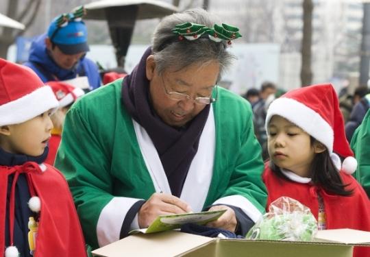 최불암 전국후원회장이 선물 박스에 넣을 손편지를 쓰고 있다.