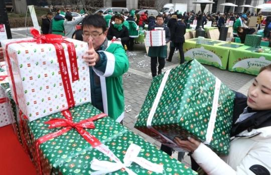 자원봉사자들이 포장된 선물을 쌓고 있다.