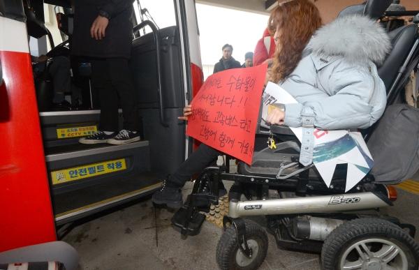 지난해 설 연휴 하루 전날인 1월 26일, 전국장애인차별철폐연대 소속 활동가가 서울 강남고속버스터미널에서 교통약자 이동편의증진법 개정을 위한 설맞이 버스타기 및 선물나누기 기자회견 후 고속버스에 탑승을 시도하고 있다.