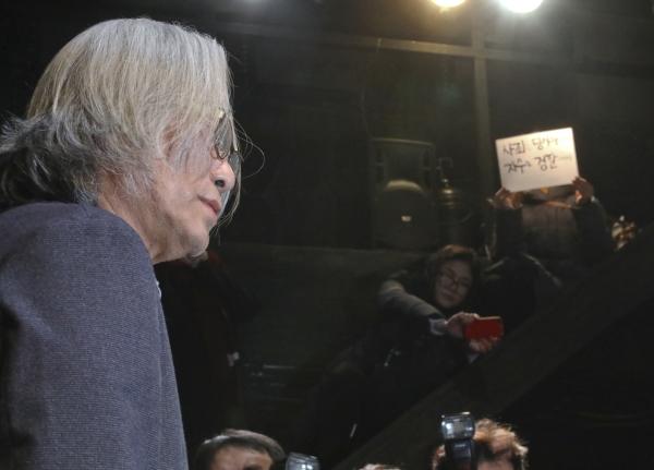 이윤택 전 연희단거리패 예술감독이 3월 19일 서울 종로구 30스튜디오에서 성추행 사실에 대한 사과 기자회견을 하고 있는 동안 한 연극배우가 '사죄는 당사자에게 하라'고 촉구하며 피켓 시위를 하고 있다. ⓒ뉴시스·여성신문