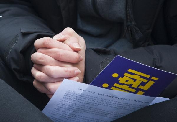 지난 1월 10일 서울 종로구 옛 주한일본대사관 앞에서 열린 '일본군성노예제 문제해결을 위한 제1317차 정기 수요시위' 현장. 한 참석자가 두 손을 꼭 맞잡고 돌아가신 피해 할머니들을 위한 묵념을 하고 있다. ⓒ이정실 여성신문 사진기자