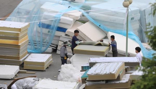 11일 오후 충남 천안시 직산읍 대진침대 본사 앞마당에서 관계자들이 방사성 물질 라돈이 검출돼 수거된 침대 매트리스 해체 작업을 하고 있다.