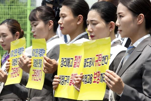 승무원 정복을 입은 KTX 해고 여승무원들이 18일 서울역 앞에서 복직과 직접 고용 문제 해결을 촉구하며 손팻말을 들고 있다. ⓒ이정실 여성신문 사진기자