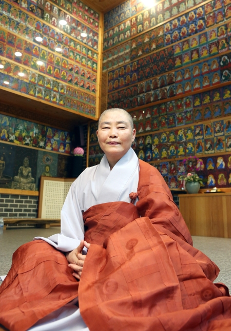 천불도 앞에 앉은 본각 스님. 천불도는 수화로 법구경의 내용을 수화로 표현하는 부처의 모습이 다채롭게 묘사했다. ⓒ이정실 여성신문 사진기자