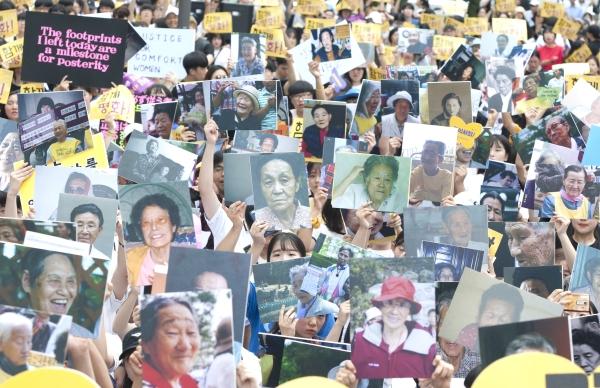 광복 73주년인 15일 서울 종로구 주한 일본대사관 앞 평화로에서 제6차 세계 일본군'위안부' 기림일 맞이 세계연대집회 및 제1348차 일본군성노예제 문제해결을 위한 정기수요시위가 열려 참가자들이 할머니 300분 사진과 함께 평화 퍼포먼스를 하고 있다. ⓒ이정실 여성신문 사진기자