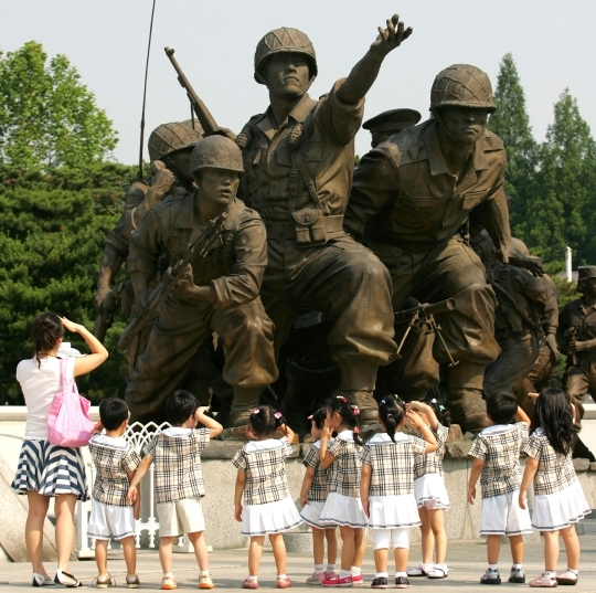 Children looking at statues of soldiers at the War Memorial of Korea in Yongsan.   ⓒ Women News DB