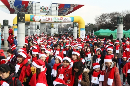 The 2013 Santa Sports Up Festival was held on the 7th at Peace Plaza in Olympic Park, Songpa-Gu, Seoul. Participants of 5km marathon in Santa outfits are passing the starting line. ⓒ Lee Jeong-sil Women's News Photographer