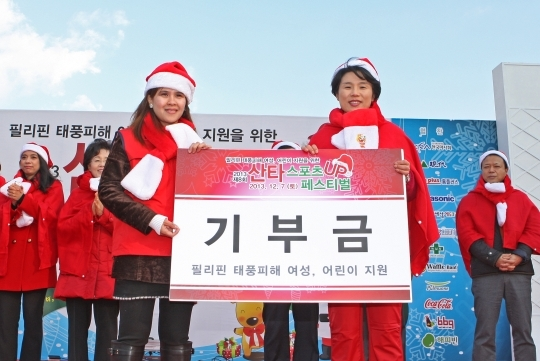 2013 Santa Sports Up Festival was held on the 7th at Peace Plaza in Olympic Park, Songpa-gu, Seoul. The festival donates part of its proceeds to the women and children of the Philippines affected by typhoon. Kim Hyo-seon, Publisher of the Women's News is handing the donation to Wendy Palomo, head of the 601 Habit. ⓒ Lee Jeong-sil Women's News Photographer