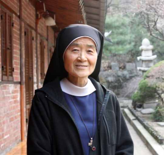 Clergywoman Okatarina smiling in the garden of the American Catholic Church of Korea located in Jung-gu, Seoul.
