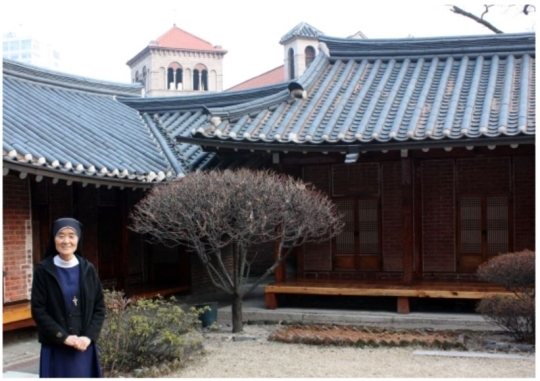 Both Western and Korean-style houses surround the Society of the Holy Cross. Okatarina is standing in front of a building.