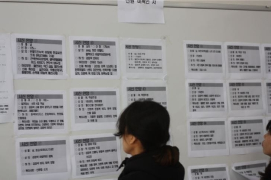 At the entrance of the gymnasium, a family member examines the list of unidentified bodies.