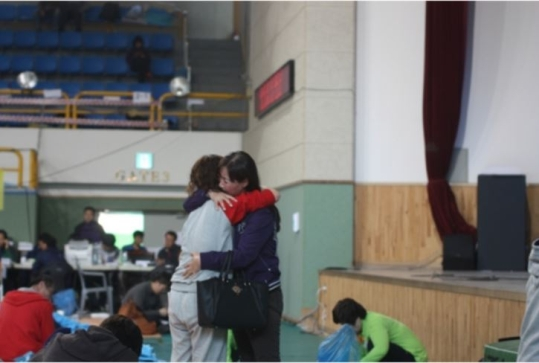 At a Jindo gymnasium, a family member of a missing passenger from the capsized ferry is being comforted by a friend.