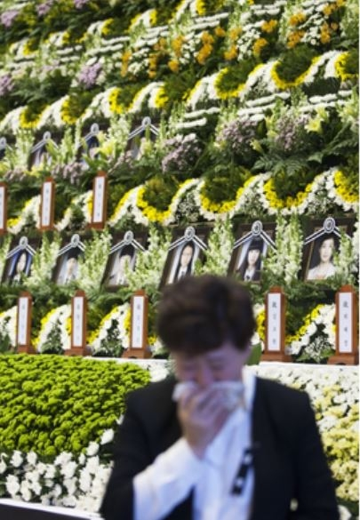 A mourner crying at the Ansan Olympic Hall, a makeshift mass memorial altar for Danwon High School students and teachers who were killed due to the sinking of the ferry Sewol.