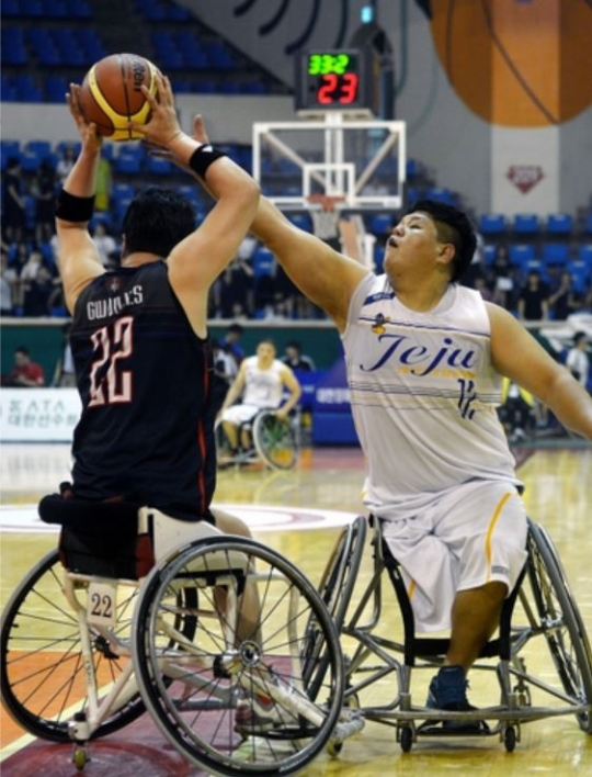 The 12th Korea Post Wheelchair Basketball Championship took place in June 2013. Kim Donghyun of the Jeju Special Self-Governing Province team and Gwon Hyungsoon of the Goyang City-Holt team are competing to grab the ball.